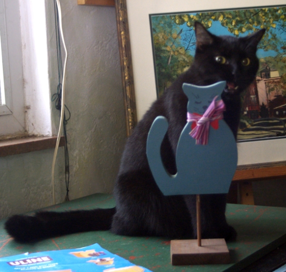black cat with blue kitty figurine