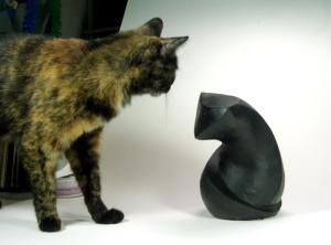 tortie cat and sculpture