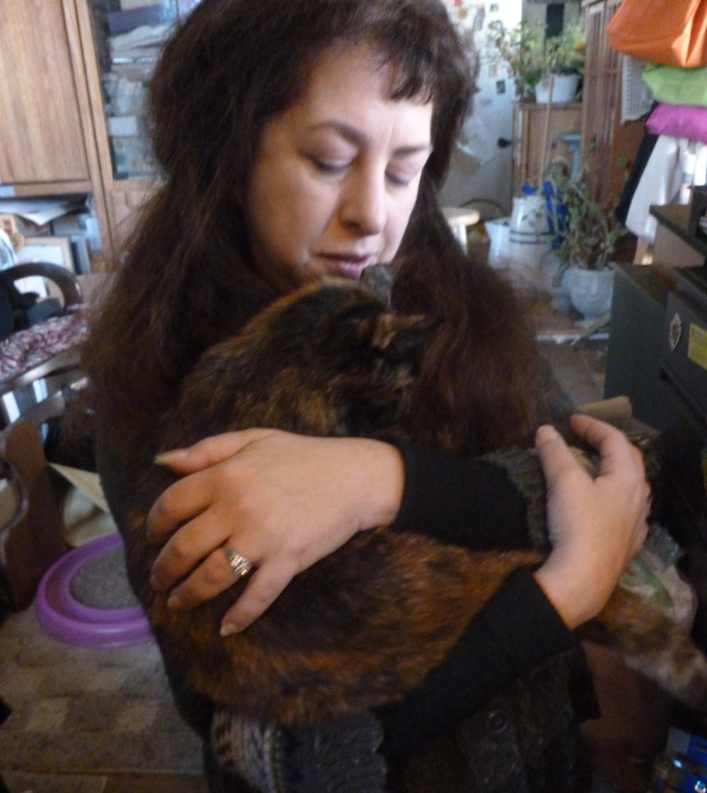 woman holding tortoiseshell cat