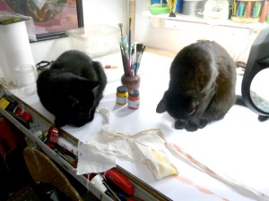 two black cats with art materials