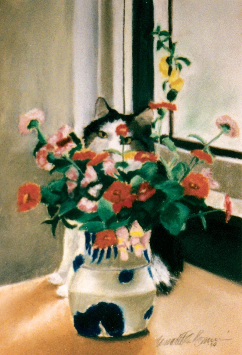 cat sitting behind vase of flowers